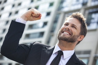 A young successful man, male executive businessman arms raised celebrating cheering shouting in fron
